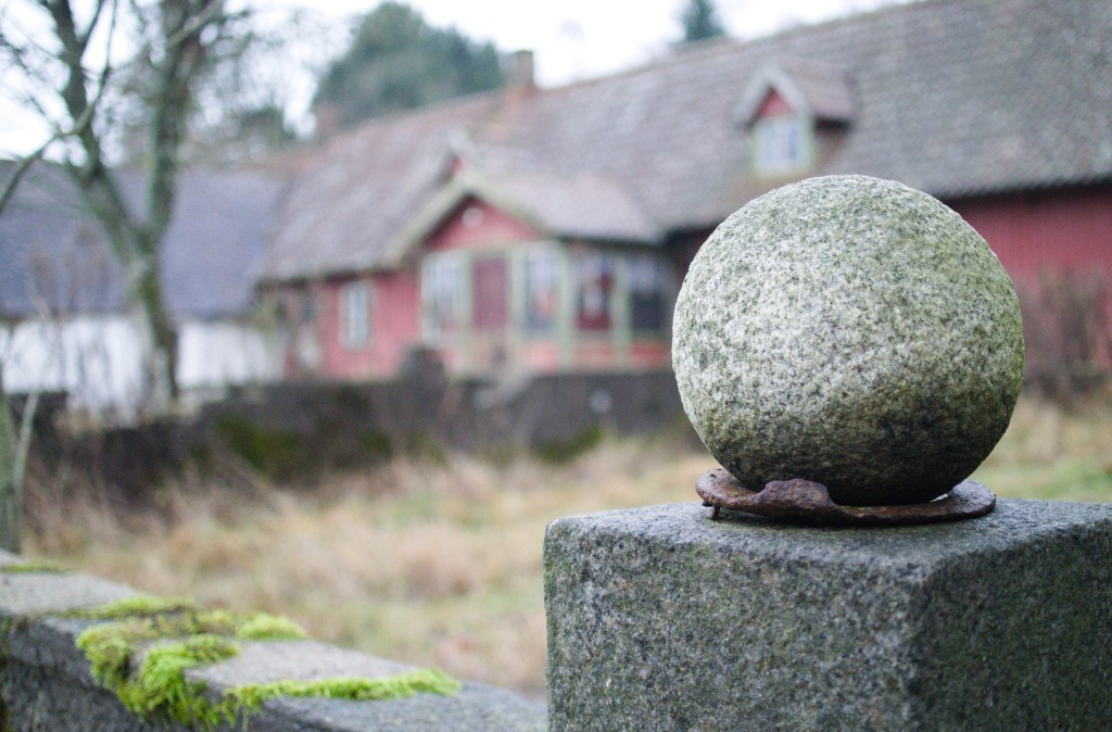 Red Swedish farmhouse in the background, mossy wall with rusted horseshoe in the foreground.